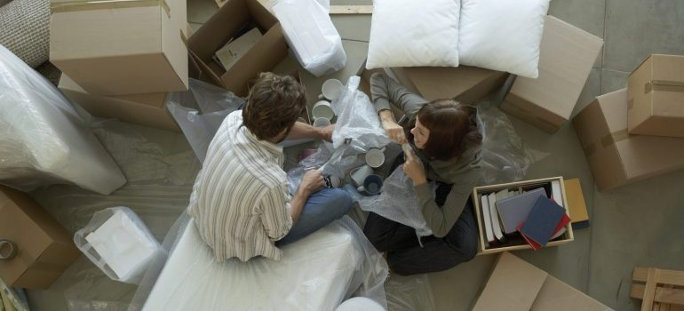 Couple surrounded by boxes packing, representing movers is potomac md