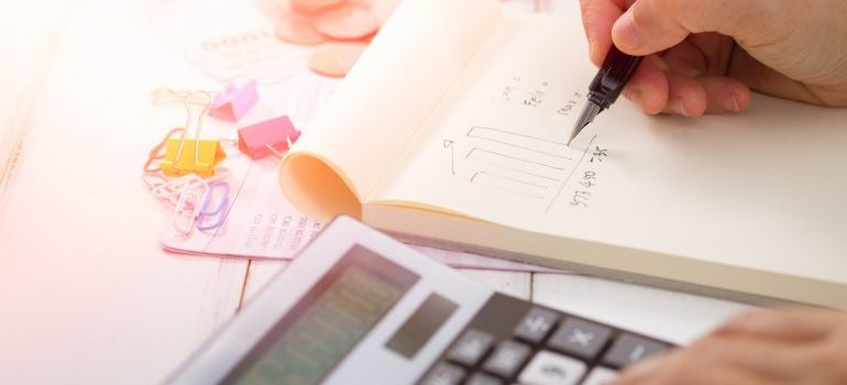 A person writing in a notebook and using a calculator - How to prepare your moving budget