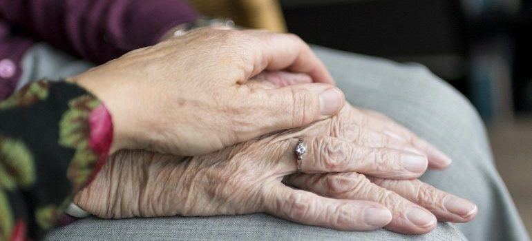 movers to help elderly people move - two elderly hands