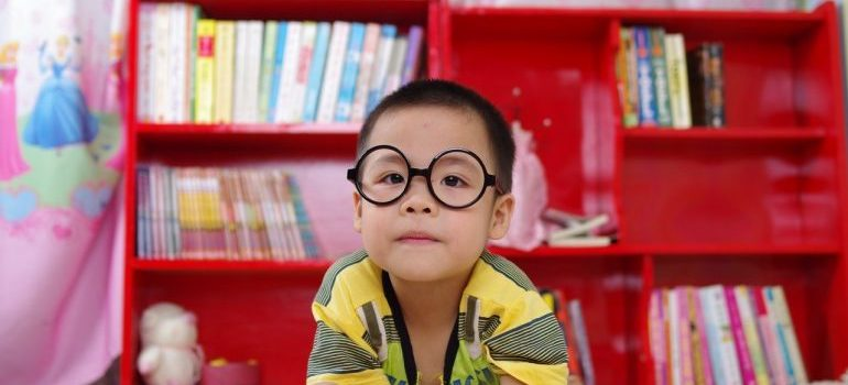 a kid with glasses and book