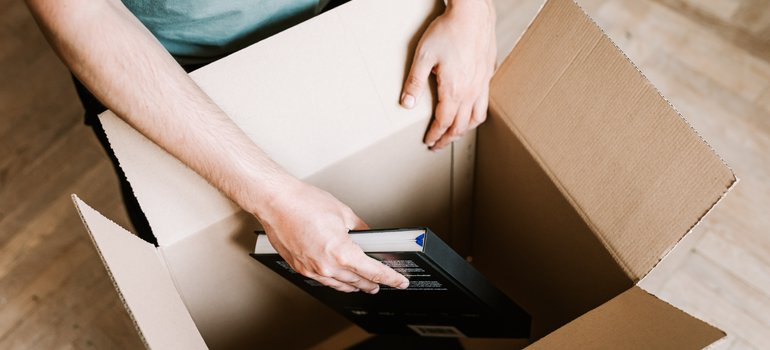 man packing books into a box