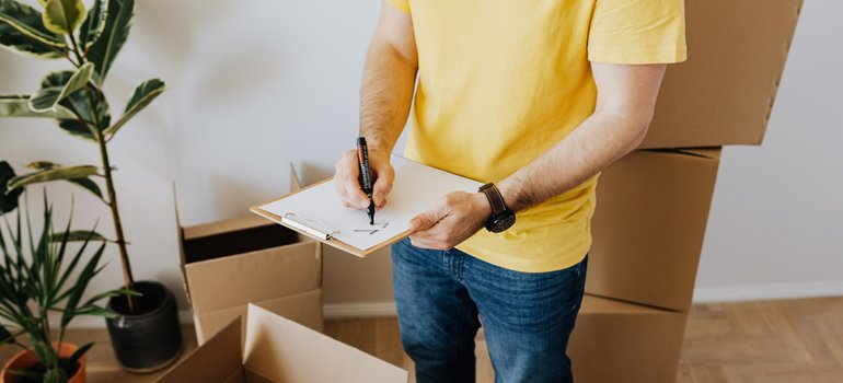 Man taking notes while packing - if you need help with packing, count on our local movers Gaithersburg MD