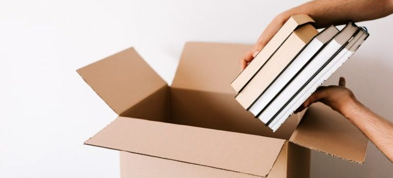 Long distance movers Gaithersburg MD packing your books into a box