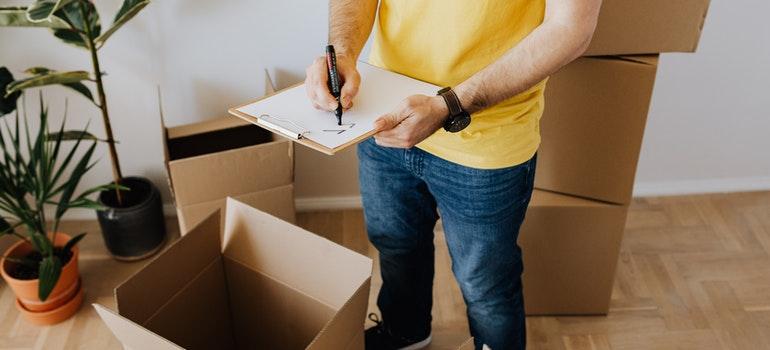 Man taking notes while packing
