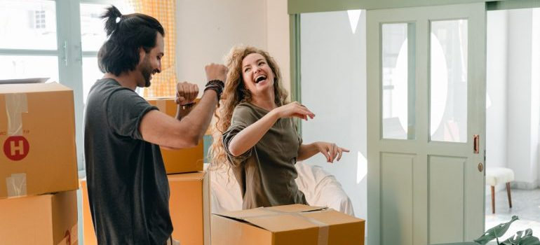 Happy couple dancing among boxes after a strainless relocation by movers in Bethesda MD.