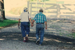 Old couple walking and holding hands