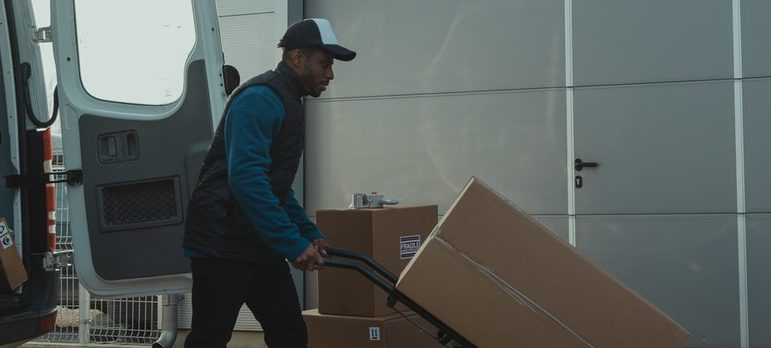 A man using a dolly to move cargo