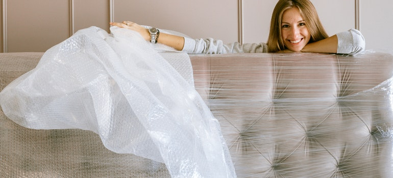 A woman is hugging a sofa wrapped in protection paper