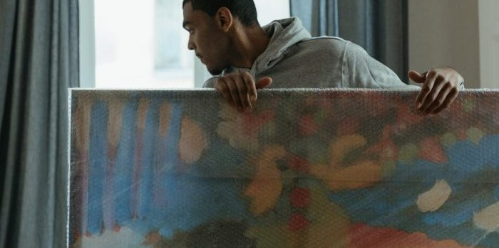 A man carrying a painting