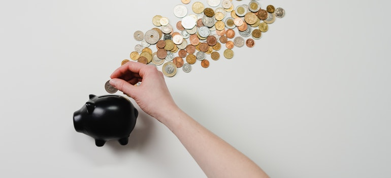 A woman is inserting a coin into a piggy bank surrounded by different coins.